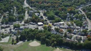 AX143_016 - 6K stock footage aerial video flying by small town, roads, shops and homes in autumn, Weymouth, Massachusetts