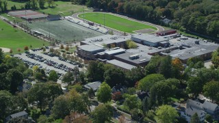 AX143_020 - 6K stock footage aerial video flying away from Hingham High School, autumn, Hingham, Massachusetts