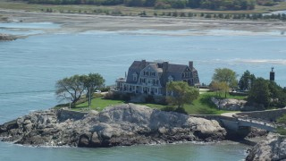 AX143_029 - 6K stock footage aerial video flying by isolated upscale oceanfront home, Cohasset, Massachusetts