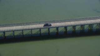 AX143_075 - 6K stock footage aerial video orbiting Powder Point Bridge, tracking a black car, Duxbury, Massachusetts
