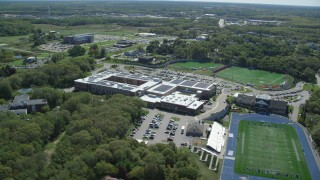 AX143_102 - 6K stock footage aerial video flying by Plymouth North High School football practice, Plymouth, Massachusetts