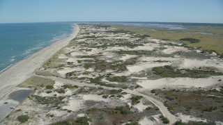 AX143_132 - 6K stock footage aerial video flying over beach, nearby sand dunes, Barnstable, Massachusetts