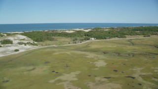 AX143_137 - 6K stock footage aerial video flying by marshland, isolated homes, coastal road, Barnstable, Massachusetts