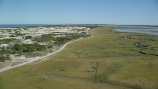 AX143_138 - 6K stock footage aerial video flying over coastal road, marshland, sand dunes, Barnstable, Massachusetts