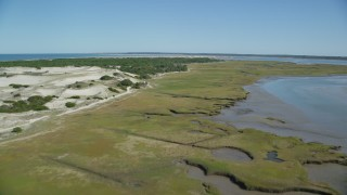 AX143_139 - 6K stock footage aerial video of an isolated home, coastal road, marshland, sand dunes, Barnstable, Massachusetts