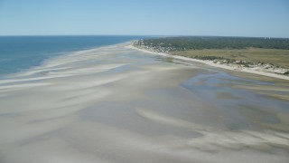 AX143_150 - 6K stock footage aerial video flying over sand bars, approach small coastal town, Cape Cod, Dennis, Massachusetts