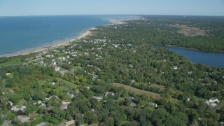 AX143_154 - 6K stock footage aerial video flying over small coastal town, green trees, Cape Cod, Dennis, Massachusetts