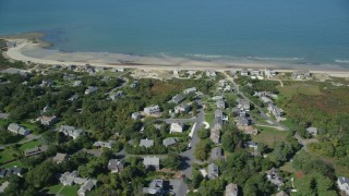 AX143_156 - 6K stock footage aerial video flying by beachfront homes, small town, Cape Cod, Dennis, Massachusetts
