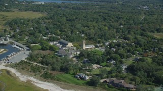 AX143_180 - 6K stock footage aerial video flying by small coastal town, Church of the Transfiguration, Orleans, Massachusetts