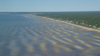 AX143_181 - 6K stock footage aerial video flying over sand bars, approaching small coastal town, Eastham, Massachusetts