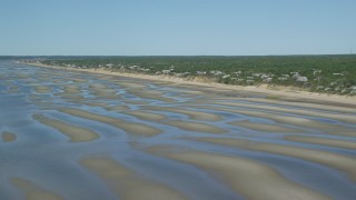 AX143_183 - 6K stock footage aerial video flying over sand bars and by beachfront homes, Eastham, Massachusetts