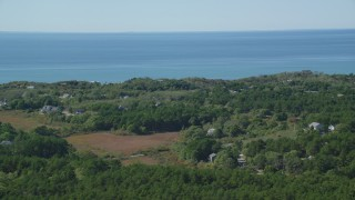 AX143_201 - 6K stock footage aerial video flying by forest, homes with ocean views, Cape Cod, Truro, Massachusetts
