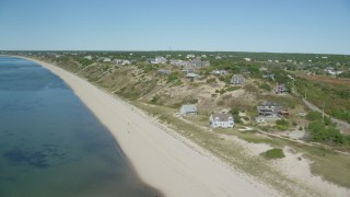 AX143_207 - 6K stock footage aerial video flying by the beach and hilltop homes with ocean views, Truro, Massachusetts