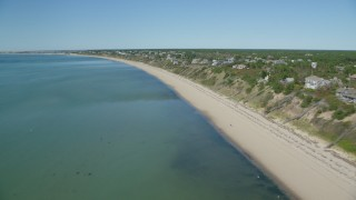 AX143_211 - 6K stock footage aerial video flying over beach, approaching homes with ocean views, Truro, Massachusetts