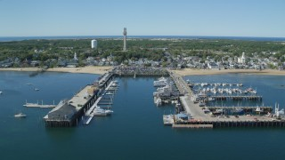 AX143_223 - 6K stock footage aerial video flying by piers, small coastal town, Cape Cod, Provincetown, Massachusetts