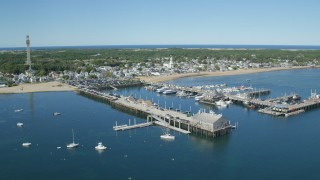 AX143_224 - 6K stock footage aerial video orbiting piers, near small coastal town, Provincetown, Massachusetts