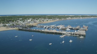 AX143_225 - 6K stock footage aerial video orbiting piers near small coastal town, Cape Cod, Provincetown, Massachusetts