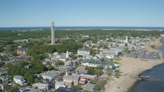 AX143_226 - 6K stock footage aerial video orbiting Pilgrim Monument, small coastal town, Provincetown, Massachusetts