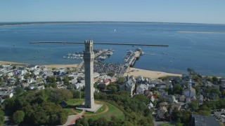 AX143_228 - 6K stock footage aerial video orbiting Pilgrim Monument, small coastal town, piers, Provincetown, Massachusetts