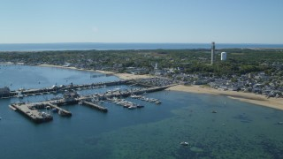AX143_231 - 6K stock footage aerial video orbiting small coastal town, piers, Provincetown, Massachusetts