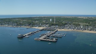 AX143_232 - 6K aerial stock footage video orbiting small coastal town, piers, Provincetown, Massachusetts