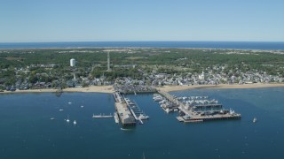 AX143_234 - 6K stock footage aerial video orbiting small coastal town, piers, Cape Cod, Provincetown, Massachusetts