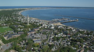 AX143_237 - 6K stock footage aerial video orbiting small coastal town, Pilgrim Monument, piers, Provincetown, Massachusetts