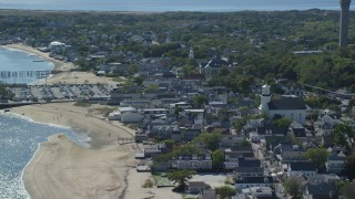AX143_241 - 6K stock footage aerial video orbiting small coastal town, reveal Pilgrim Monument, Provincetown, Massachusetts