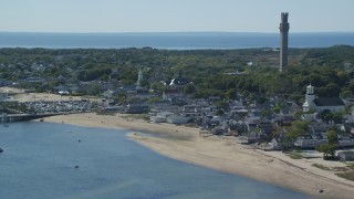AX143_242 - 6K stock footage aerial video of a small coastal town, Pilgrim Monument, reveal piers, Provincetown, Massachusetts