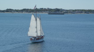 AX143_244 - 6K stock footage aerial video orbiting sailing boat, revealing Pilgrim Monument and Provincetown, Massachusetts