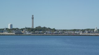 AX143_245 - 6K stock footage aerial video flying by small coastal town, Pilgrim Monument, Provincetown, Massachusetts
