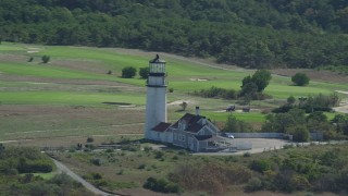 AX144_015 - 6K stock footage aerial video flying by Highland Light, dense forest, Cape Cod, Truro, Massachusetts