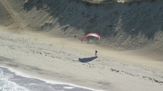 AX144_026 - 6K stock footage aerial video flying by parachuter on the beach, Cape Cod, Wellfleet, Massachusetts