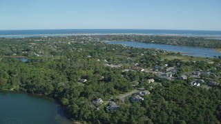AX144_052 - 6K stock footage aerial video flying by small coastal town, dense green trees, Chatham, Massachusetts