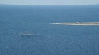 AX144_071 - 6K stock footage aerial video of a Coast Guard helicopter, rescue practice, Great point Light, Nantucket, Massachusetts
