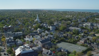 AX144_083 - 6K stock footage aerial video flying by small coastal town, approaching church, Nantucket, Massachusetts