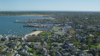 AX144_087 - 6K stock footage aerial video flying by small coastal town, Nantucket Harbor, Nantucket, Massachusetts