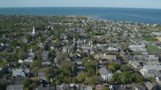 AX144_101 - 6K stock footage aerial video flying over small coastal community, harbor in the distance, Nantucket, Massachusetts