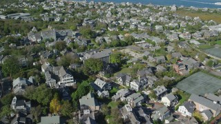 AX144_102 - 6K stock footage aerial video flying by small coastal community, tilt down, Nantucket, Massachusetts