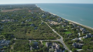 AX144_105 - 6K stock footage aerial video flying over small island town, beachfront upscale homes, Nantucket, Massachusetts