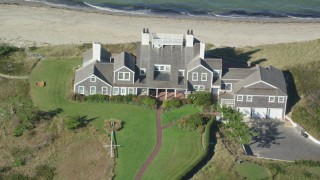 AX144_107 - 6K stock footage aerial video flying by upscale beachfront homes, tilt down, Nantucket, Massachusetts
