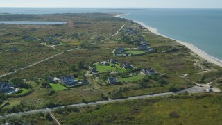 AX144_109 - 6K stock footage aerial video flying over upscale beachfront homes, coastal community, Nantucket, Massachusetts