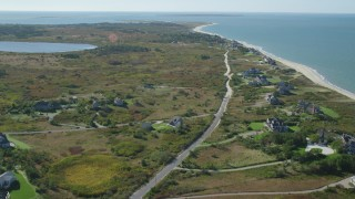 AX144_110 - 6K stock footage aerial video flying over upscale beachfront homes, pan right, Nantucket, Massachusetts