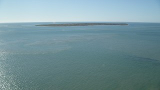 AX144_115 - 6K stock footage aerial video flying over the ocean approaching Tuckernuck Island, Nantucket, Massachusetts