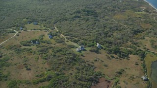 AX144_118 - 6K stock footage aerial video approaching, tilt down on homes, Tuckernuck Island, Nantucket, Massachusetts