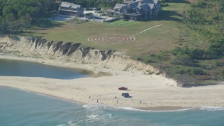 AX144_124 - 6K stock footage aerial video of an isolated beachfront mansion, trucks on beach, Chappaquiddick Island, Martha's Vineyard, Massachusetts