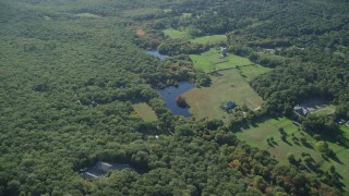 AX144_156 - 6K stock footage aerial video over rural homes, approach ponds, West Tisbury, Martha's Vineyard, Massachusetts