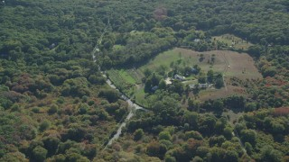 AX144_158 - 6K stock footage aerial video flying by small farm, dense trees, Chilmark, Martha's Vineyard, Massachusetts
