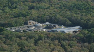 AX144_211 - 6k stock footage aerial video flying by water treatment plant, dense trees, Dartmouth, Massachusetts
