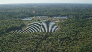 AX144_212 - 6k stock footage aerial video approaching solar array, dense trees, Dartmouth, Massachusetts